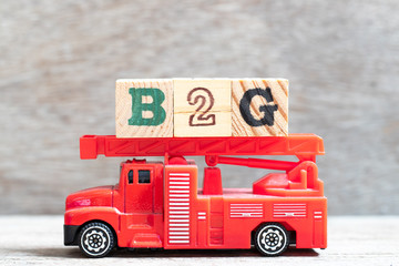 Red fire truck hold letter block in word B2G (abbreviation of business to government) on wood background