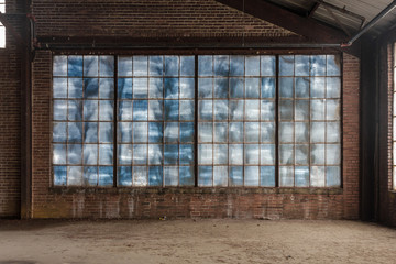 Ingelijste posters Oude verlaten gebouwen Large blue frosted windows in a loft like space of an abandoned factory with brick walls