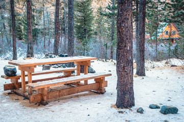 Wooden bench and table in forest. Camping in winter forest