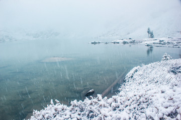Lakeside under fresh snow. Winter snowfall on river
