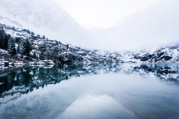 Reflection of peaks in mountain lake. Snowy winter in mountain valley