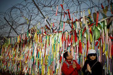Tourists pose for photographs near a military fence decorated with ribbons bearing messages wishing for reunification near the demilitarized zone separating the two Koreas in Paju
