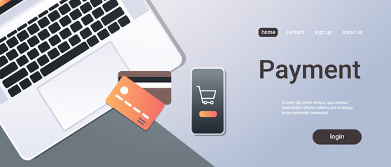 online shopping mobile application internet payment concept top angle view desktop smartphone laptop screen credit card office stuff horizontal copy space