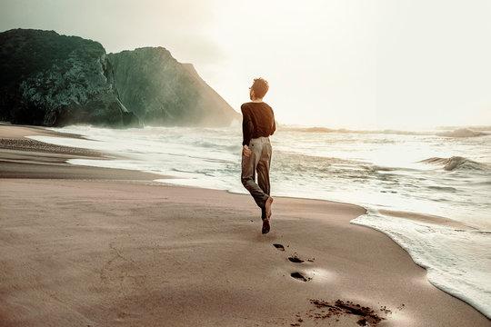 Young man dancing along the shore line