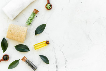 Tea tree spa composition. Fresh tea tree leaves, natural cosmetics, towel on white stone background top view copy space border