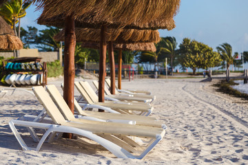 Beach chairs on a white sand beach with a palapa style umbrella.