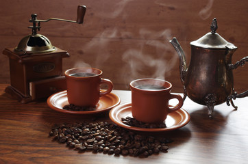 Two cups of hot coffee with steam, coffee grinder, coffee beans on the table
