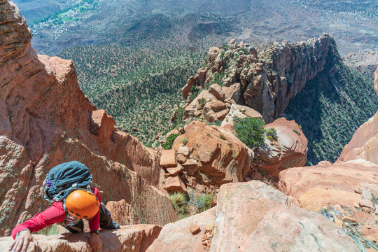 Top down perspective of Woman Climbing Cowboy Ridge in Zion National Park with exposure and heights. Orange Sandstone ridge in Utah