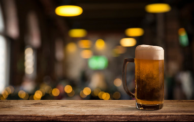 Glasses with cold beer on table against blurred background
