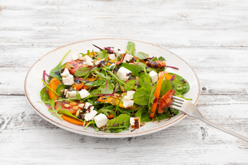 Salad (arugula, chard, mustard salad, spinach, persimmon, red orange, feta cheese, roasted pumpkin seeds, balsamic sauce cream) on white wooden background, top view