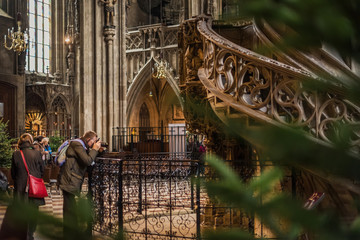 Vienna, Austria - December 30, 2017. Man taking picture with his camera inside Saint Stephen's Cathedral with christmas decoration. Church interior with visitors by winter holidays.