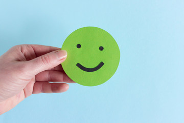 Crop hand with positive green smiley