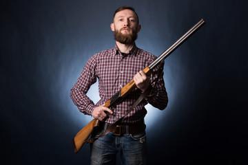 Man holds in his hand old shotgun. Dark blue background. Man with shotgun on a dark background
