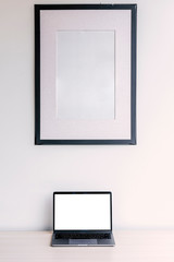 Blank picture frame and laptop on wooden table
