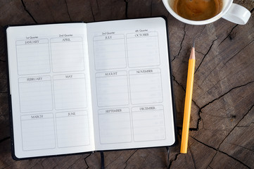 Top view of open page diary with yellow pencil and cup of coffee on wooden background.