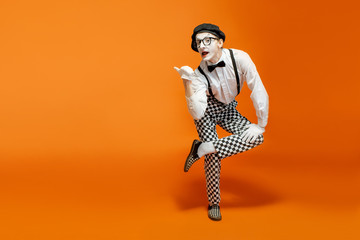 Emotional pantomime with white facial makeup showing empty space on the orange background, advertising something Wall mural