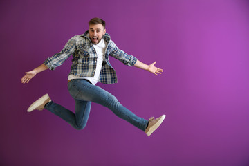 Jumping young man on color background Wall mural