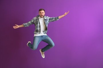 Jumping young man on color background