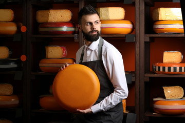Male seller with delicious cheese in store