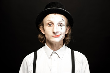 Portrait of a pantomime with a make-up on the one side of his face on the black background. Concept of a personality split
