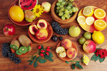 A variety of fruits on the dishes on the table. Grapes, peaches, apples, lemon, orange, pomegranate, pears, plums.