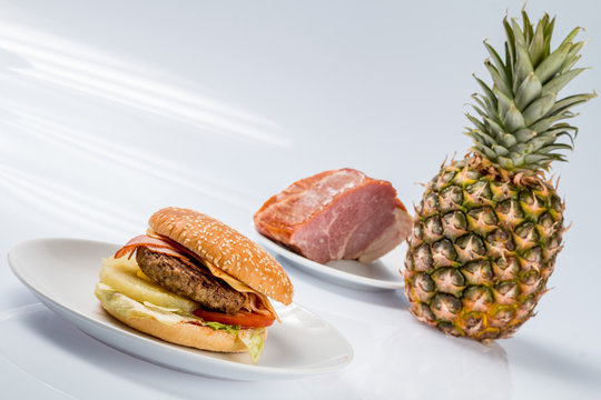 cheeseburger with pineapple on a plate with fresh bacon and ripe pineapple