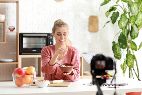 Young female food blogger recording video indoors