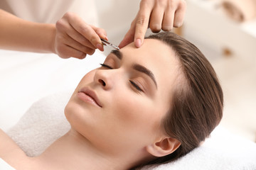Young woman undergoing eyebrow correction procedure in beauty salon