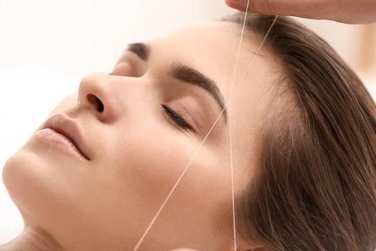 Young woman undergoing eyebrow correction procedure in beauty salon