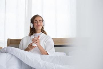 Woman holding glass of milk and listening relax song at music application in the morning on the bed in the room at condominium