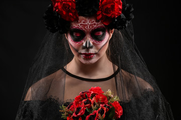 Young woman with painted skull on her face for Mexico's Day of the Dead against dark background