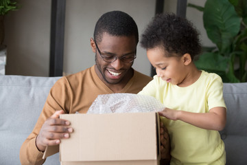 Happy black father and little kid son open cardboard box