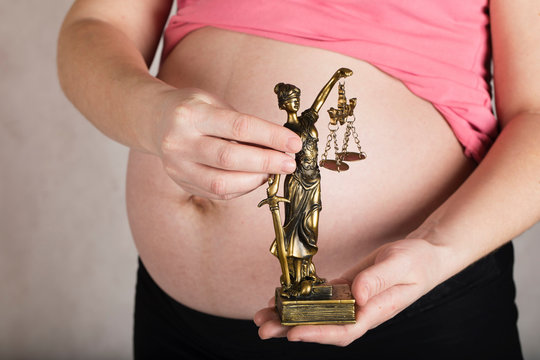 Young pregnant woman keeps statue of Themis.
