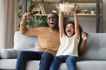 Happy overjoyed black father with kid daughter watching tv game