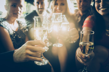 Party crowd clinking glasses with champagne