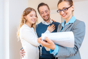 Realtor lady filling in details on new lease contract for apartment