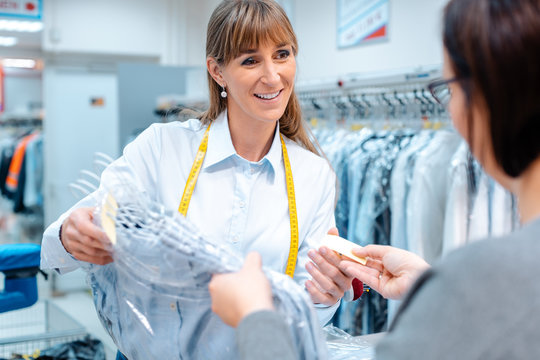 Customer in dry-cleaner shop getting back her clothes