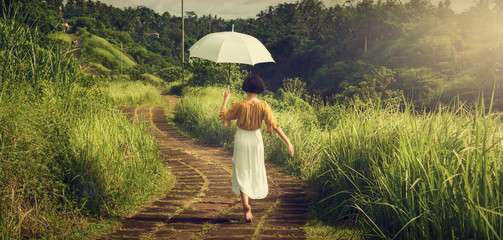 A girl in a white dress on the path of the artist. Girl with an umbrella. Bali trip. Tropics. Campuhan Ridge Walk Travel.