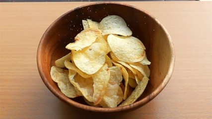 Fototapete - Sprinkle salt on a pile of potato chips in a wooden bowl in Slow Motion