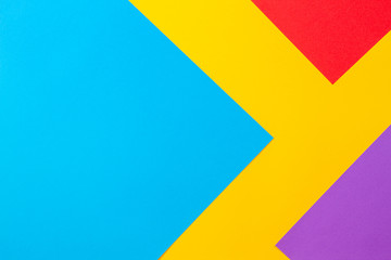 Color papers geometry flat composition background with yellow red blue and purple tones