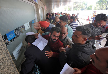 Passengers crowd a ticket counter outside the airport after their flight was cancelled following temporarily suspension of flights, in Jammu
