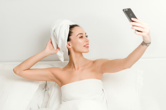 Beautiful young woman wrapped in towels waking in the morning making a selfie in bed. lifestyle concept