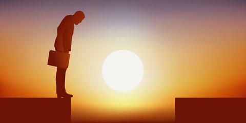 Concept de l'échec avec un homme dans une impasse, debout au bord d'un gouffre qui l'empéche de rejoindre la rive opposée et le force à renoncer devant l'obstacle.