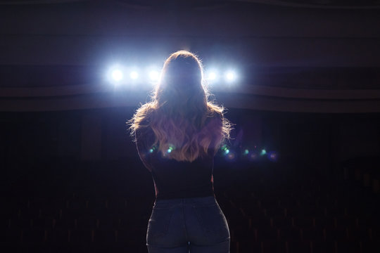 unrecognizable singer standing on stage at microphone in night club, back view