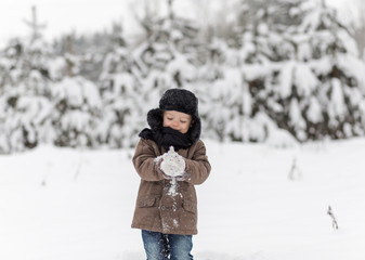 little boy playing snowballs in winter in nature