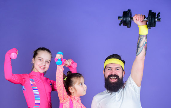 Lets practice. Sports coach and little girls building strength with dumbbells. Father and daughters exercising in gym class. Happy family training in gym class. Father and children having gym workout