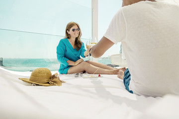 beautiful happy young couple holding glasses of champagne and resting near sea