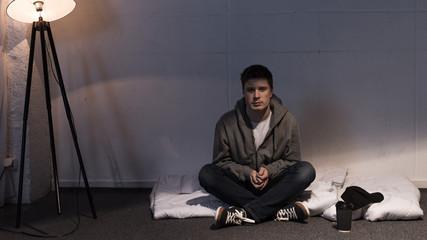 man sitting on white mattress arranged on floor in dark room
