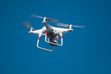 closeup of white quadcopter drone for video appllcation in outdoor on blue sky background