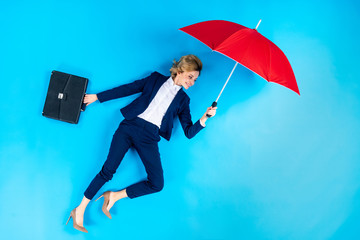Woman with briefcase posing with red umbrella on blue background
